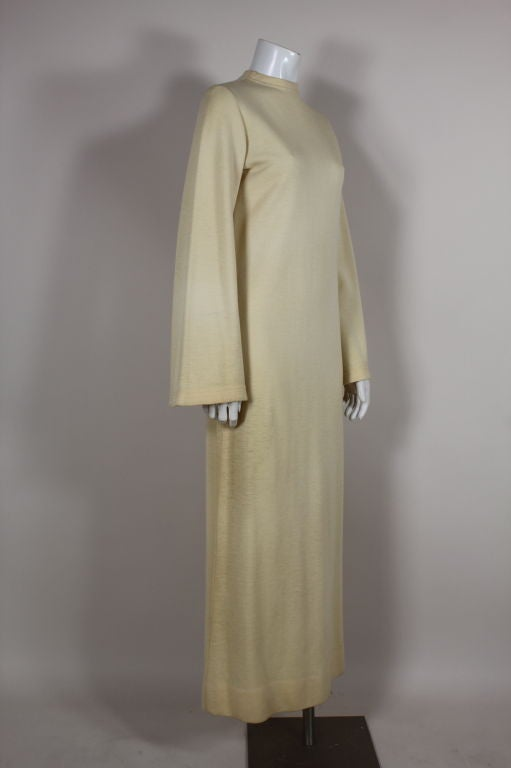 Iconic and streamlined circa late 1960s/early 1970s ivory double knit wool maxi from Rudi Gernreich features a high rounded neck and long bell sleeves. Zip back.