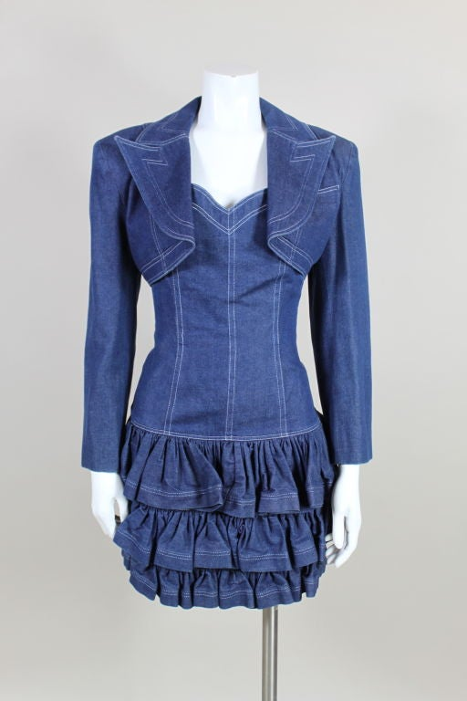 Super sassy, fit and flared, denim mini dress from Patrick Kelly features a sweetheart neckline and a body-hugging silhouette with a tiered ruffle skirt. Decorative, contrasting topstitching accents all seam-lines. Matching cropped jacket has an