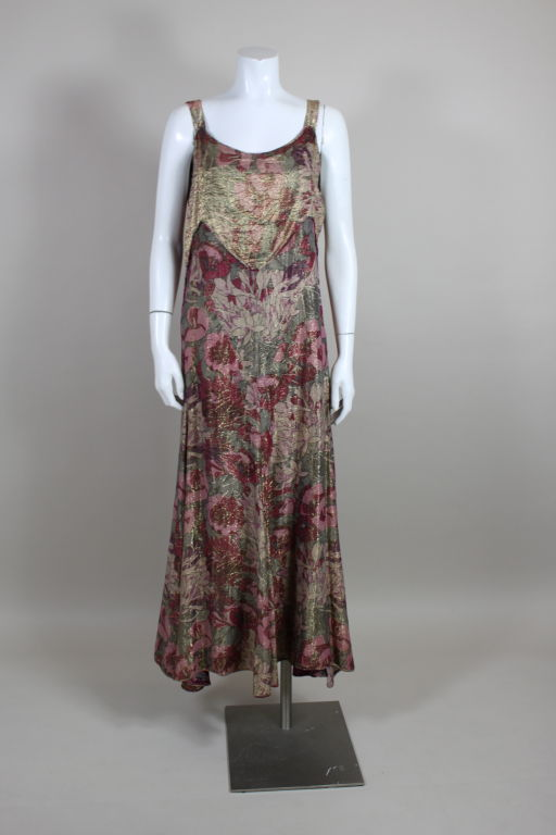 Show-stopping, Deco lamé gown features a William Morris-inspired floral in shades of wine red, lavender, sage green, and ivory. Sleeveless gown has a scalloped bodice panel and a flared godet skirt. Meant to be worn loose.