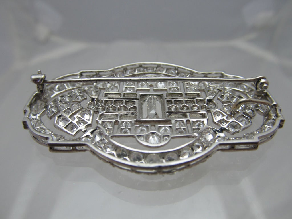 PLATINUM ART DECO DIAMOND PIN, CENTER VERTICAL BAGUETTES, SIDES BRILLIANT CUTS, BAGUETTES AND FACETED HALF MOONS WEIGHING APPROXIMATELY 9 - 10 CT  Measurements: length: 2 inches/ 5 cm width: 1.75 inches/ 3.5 cm