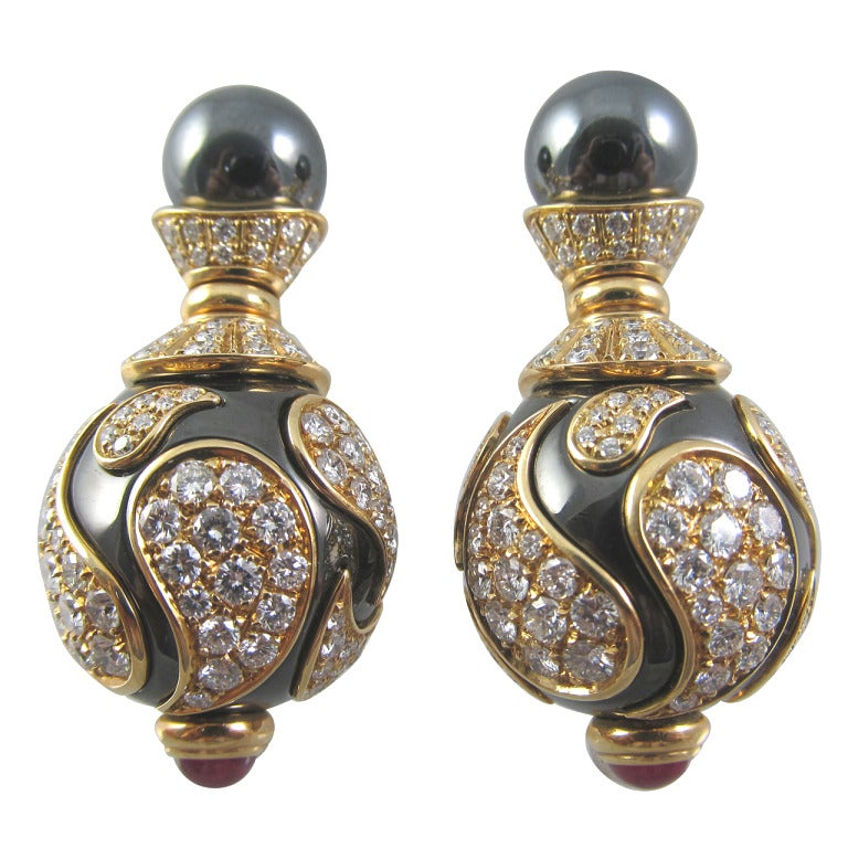 "Impressive Chopard earrings Chopard ""Casmir"" collection, diamond and ruby earrings.  Impressive Chopard diamond & hematite earrings with small hematite ball on top of a hour-glass design 18k yellow gold encrusted with 266 round"