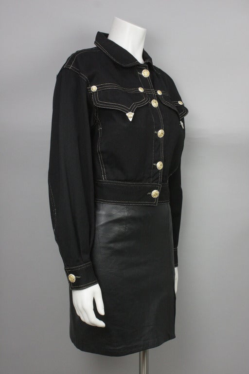 Black denim jacket with gold top stitching and signature Medusa head buttons accented with rhinestones. Two breast pockets with Western style tips-- also with Medusa head-- at the pointed flaps.