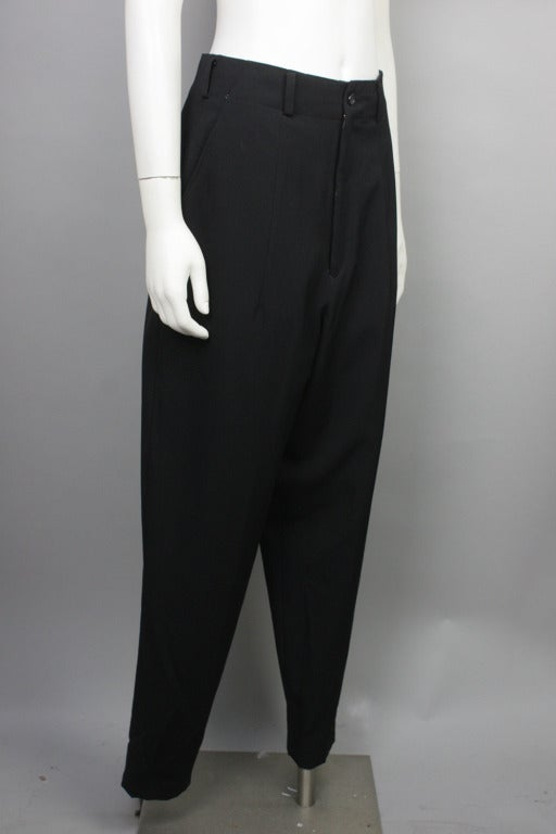 15% OFF! Originally $395  Black pants with a high waist, low crotch, and tapered leg. Two front pockets. 100% wool.