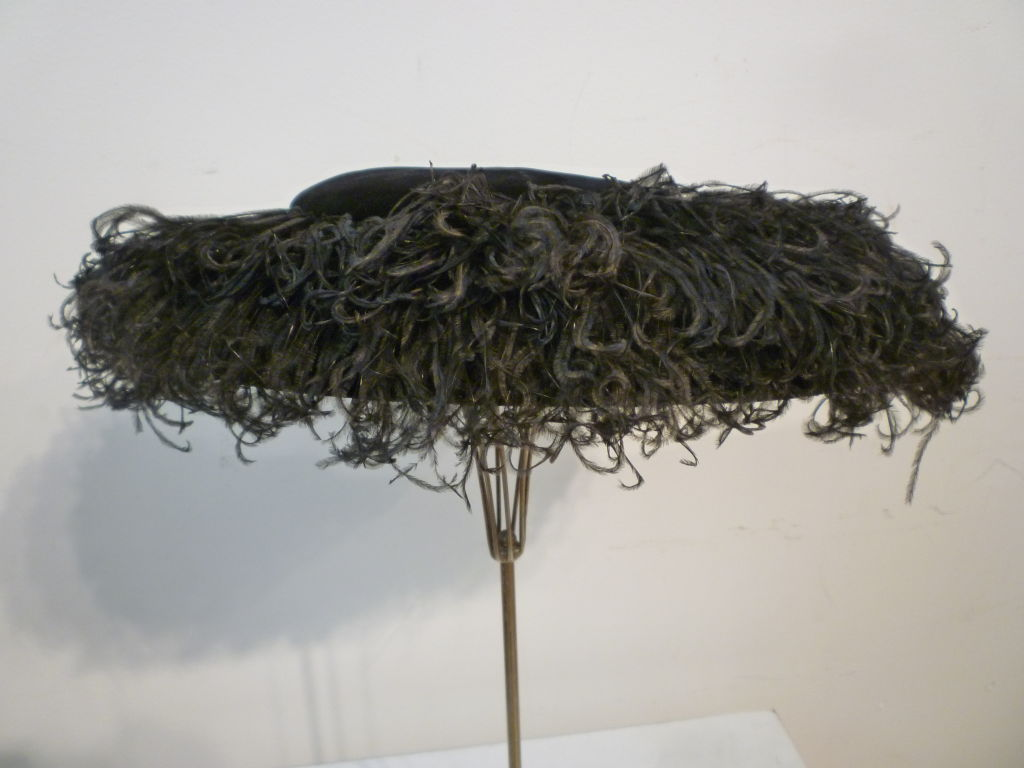 "This is a spectacular 1950s evening/cocktail portrait hat from Saks Fifth Avenue in black silk velvet with a copious supply of ostrich feathers. Includes two small combs attached for securing to the head.  One size fits all.  Measures 18"" wide"
