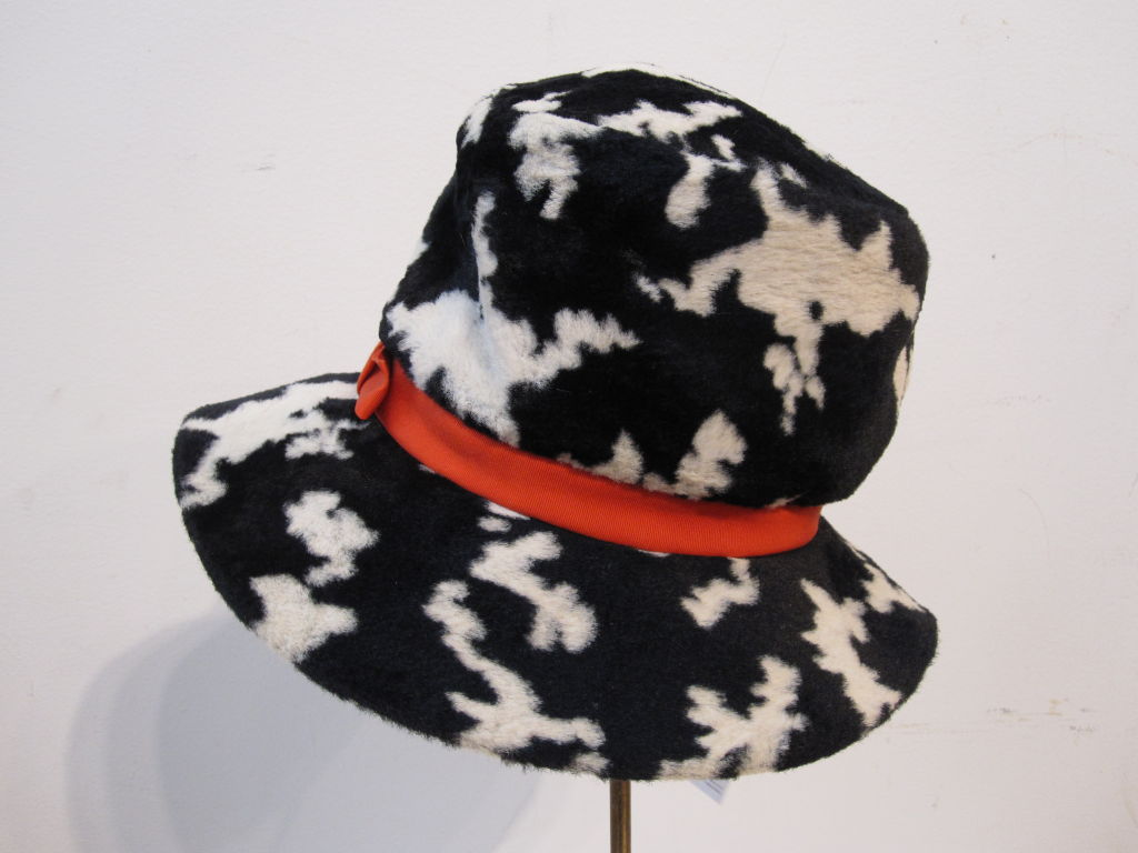 "A wonderfully mod ""Dachettes"" hat by Lilly Dache in black/white faux fur with an orange silk band. Measures 20.5"" around inner band."