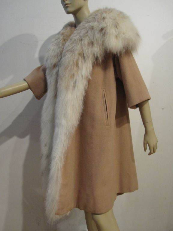 A beautiful 1950s I. Magnin camel colored cashmere trapeze coat with 3/4 sleeves, silk lining and extravagain lynx collar and detailing. Size 4-6.