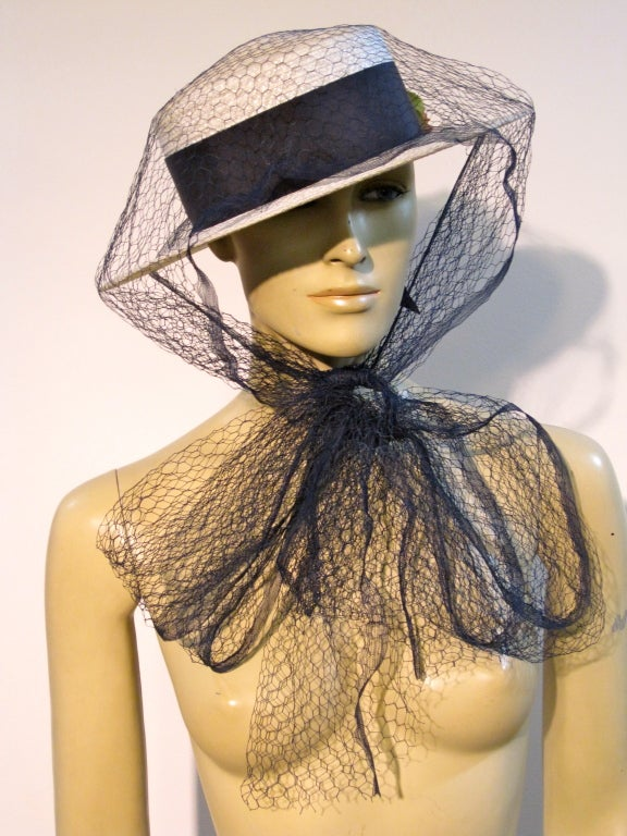 An adorable 1950s Coralie white straw boater hat with navy blue grosgrain band, silk flower and navy tulle tying veil. Size 22.