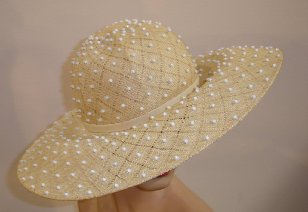 """A fantastic Irene of New York 1950s hat, made in an unusual weave with open spaces in a diamond pattern and dotted all over with white enameled metal studs.  Brim measures 5"""" wide and 21.5"""" around inner grosgrain band."""