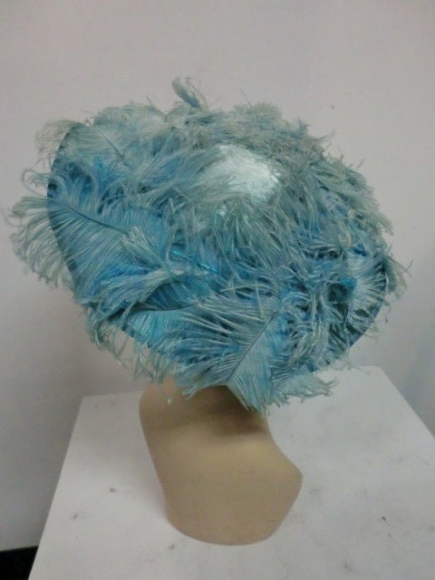 A fantastic 1950s cocktail hat in a long-nap silk and mohair faux fur fabric by Flo-Raye, covered in pale aqua ostrich feathers!  Absolutely gorgeous!  One Size.
