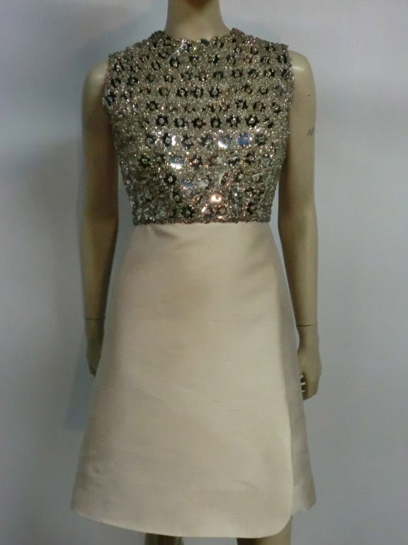 "A beautiful 60s ivory shantung silk A-Line dress with molded, fitted capelet and extravagantly beaded and sequined ""Mirror"" bodice in silver."