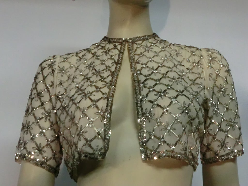 A beautiful little 40s silk bolero jacket in white with silver and gold toned sequins and embroidery arranged in a trellis style pattern.  Lined.