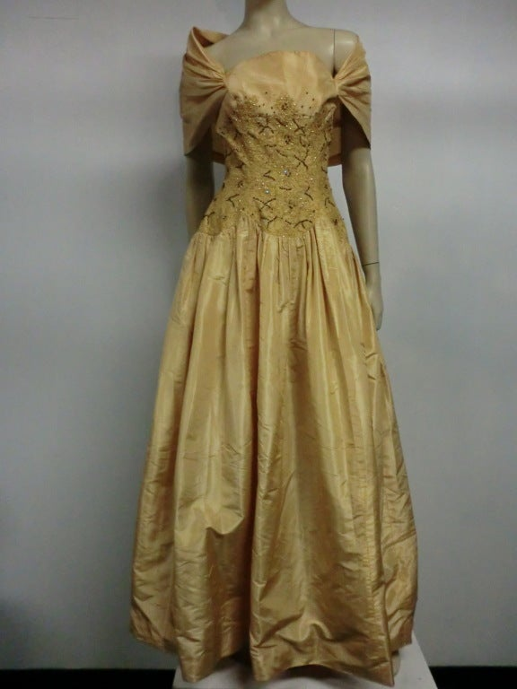 A beautiful 50s beaded and embroidered bodice gown in pale gold tissue silk.  Dropped waist with gathered skirt and portrait