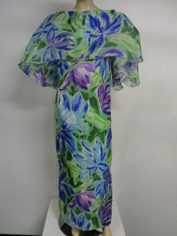A fantastic late 70s silk organza column gown in oversized floral print in blues, purples and greens with a flowing, fluttering capelet with horsehair braid under-construction cascading down the back.