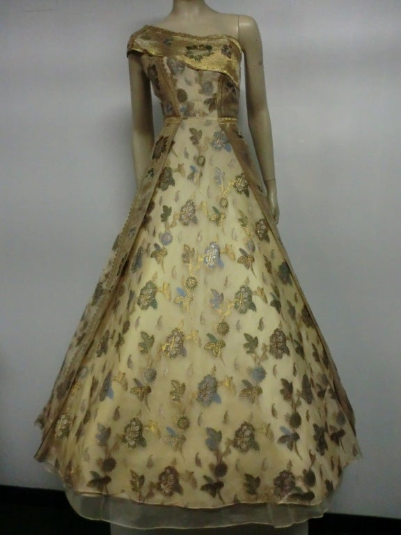 A wonderful 1950s one-shoulder gown made of gold, silver, and cornflower blue floral brocade organza sari fabric.  Beautifully structured bodice utilizes sari edging for a delicious sash at the shoulder, and the double layered skirt interior is