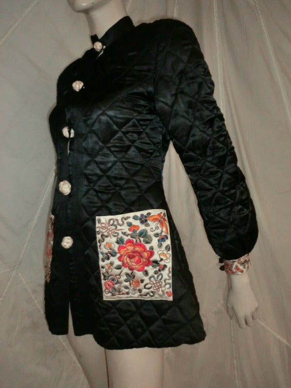 An adorable 20's/30's black silk satin quilted Chinese jacket with Nehru style collar and silk knot buttons in ivory.  The banded cuffs on sleeves and front pockets are all hand embroidered. Lined.