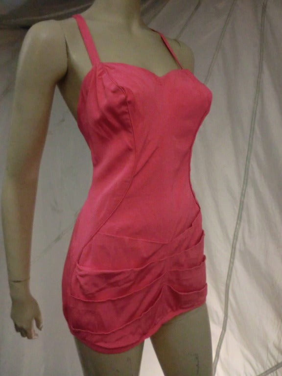 """A fantastic 1950's Catalina one-piece """"pin-up"""" style bathing suit in bubblegum pink with low cut back, and apron style cut.  Beautiful tucks at hips."""