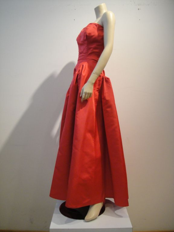 This striking Pauline Trigere strapless asymmetrical 1950s silk taffeta gown in a fresh reddish pink color is intricately structured with double layered bodice, a double zipper, and a weighted lining.  It also includes a matching taffeta wrap not