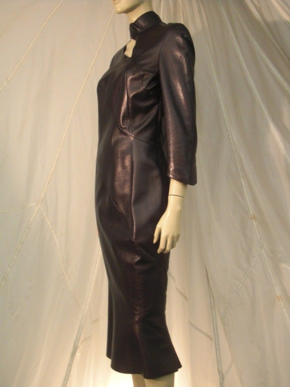 A sexy 1980s Thierry Mugler sculpted leather dress in black with high collar and provocative slit at décolletage.  3/4 length sleeve and slightly flared at hem.