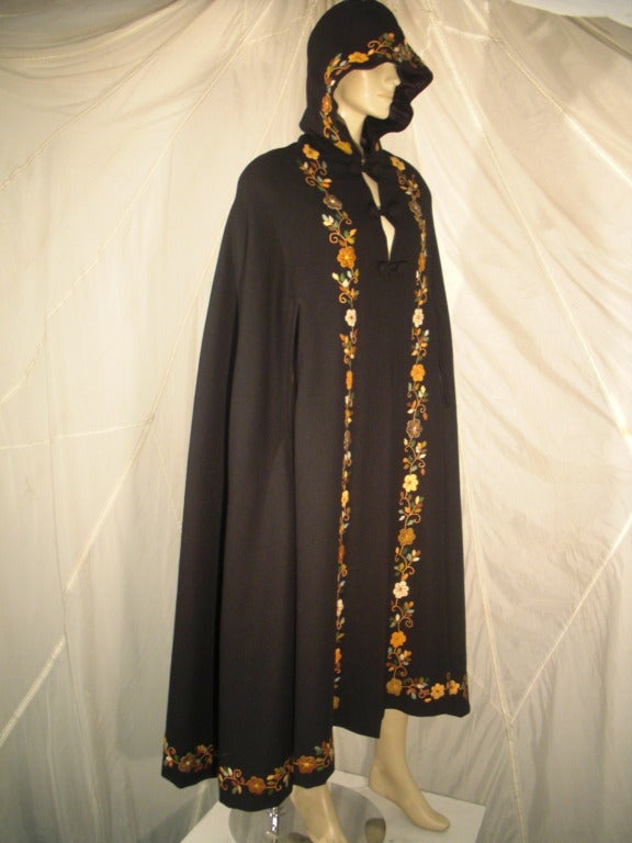 A beautiful 1970s lightweight black wool cape: Satin lined with crewel-work Tree of Life design on back.  Full swing cut.   Lined hood and double button and loop closures.