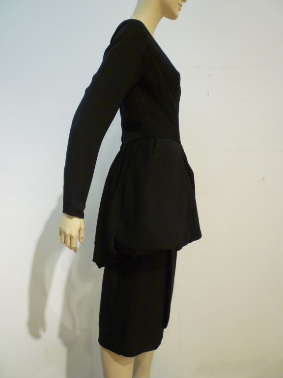 Ultra-chic 50s Ceil Chapman cocktail dress in black crepe with a wide ballet neckline, full length sleeves, a tulip hemmed wrap skirt and balloon hemmed peplum.  This is a gorgeous silhouette from a designer of the highest caliber!