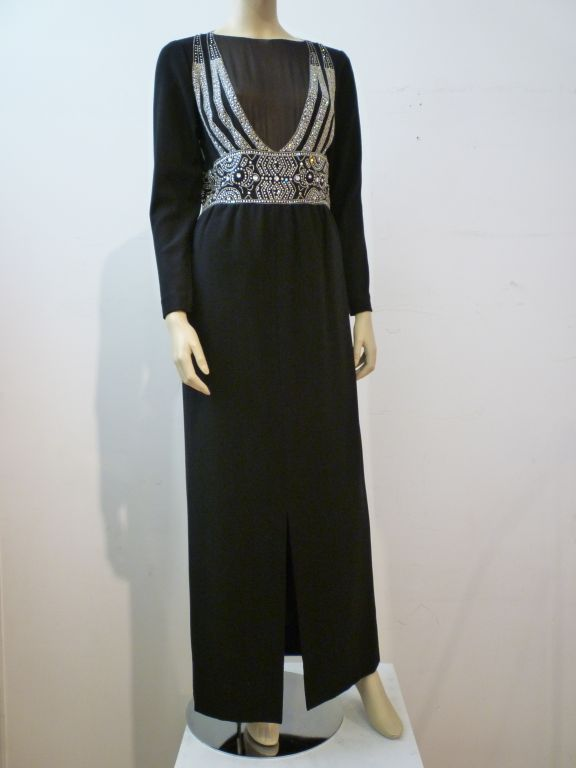 A gorgeous and elegant Pauline Trigere Art Deco Revival style gown with rhinestone and bead embellished neckline and waist, sheer black chiffon front and back panels in the bodice. Front center slit and full sleeves. Back zipper.