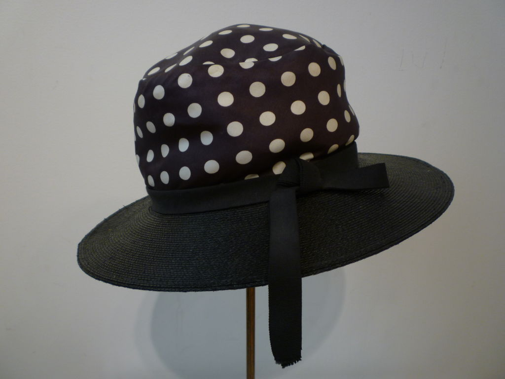 A wonderful Joseph Magnin 1960s summer hat in navy blue straw and navy/white silk satin covered crown.  Trimmed with navy grosgrain band.