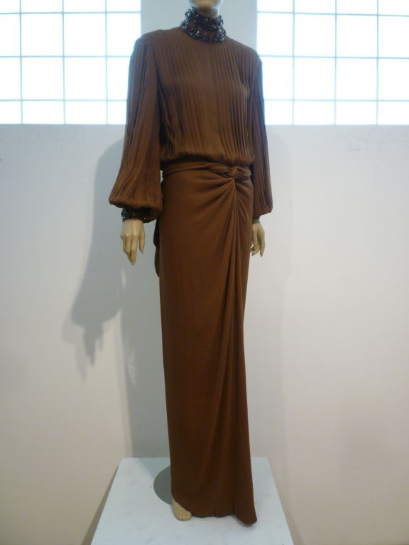 A fantastic brown silk chiffon evening gown from James Galanos with draped column skirt and pleated bodice and balloon sleeves.  Neckline and cuffs are embellished with gray, silver and topaz color beading.