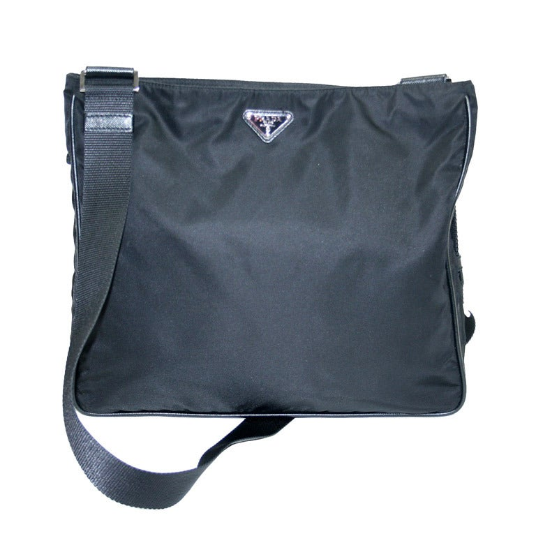 Prada Black Vela nylon Prada crossbody bag with silver-tone hardware, tonal woven adjustable flat shoulder strap, single zip pocket and logo placard at front, tonal nylon lining and zip closure at top.