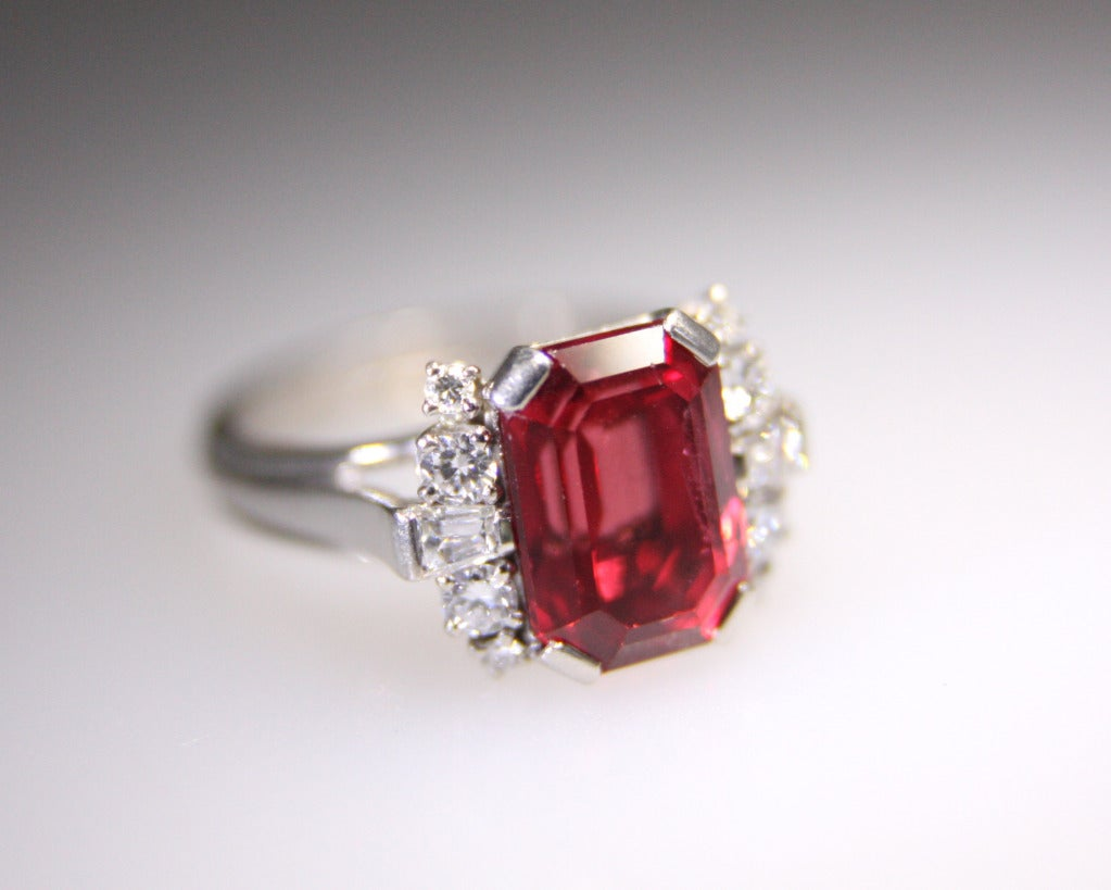 The ring made by Gubelin has a red emerald cut spinel weighing approximately 5.50 carats. It is further set with 8 round and 2 baguette-cut diamonds. Mounted in Palladium. Size 6 1/2.  Can be sized.
