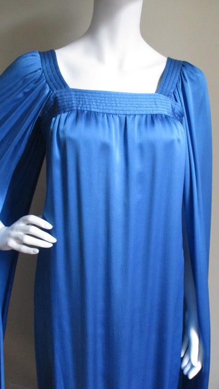 Beautiful azure blue scarf weight silk charmeuse dress from Marc Bohan for Christian Dior Couture. The neckline is square and finished in lines of trapunto embroidery from which gathered floor length angel sleeves emanate. There is a hand sewn side