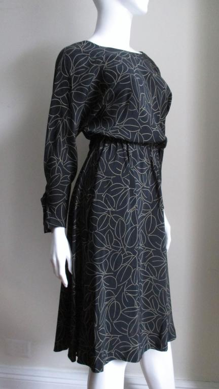 A great black wrap silk abstract leaf patterned dress from Halston.  The dress has a rounded front neck and a V in the back.  It wraps crossing at the back closing with black hooks at the waist.   It has dolman sleeves and the skirt is full.  The