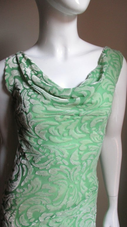 A great silk cut velvet dress from Gianni Versace in a pretty light green with an abstract scrolls, feathers and leaves pattern.  It is cut on the bias for a great fit on the wearer and has a draped neckline front and back.  The skirt portion fits
