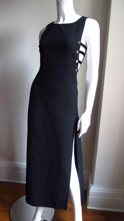 A statement making dress from Courreges in black cotton pique.  Simple dress enhanced with sides cut out to just below the waist.  Strips of fabric with stretch hold the front to the back on both sides and are attached to the dress with square