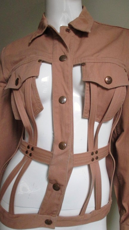Junior Gaultier clay colored cotton twill cage jacket with lots of detail.  It is a fitted waist cinching jacket.  The front is a cross section of rows of angled boning the length of the jacket and around the front waist. There are 4 brass studs
