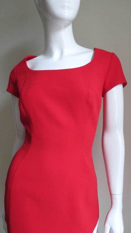 Fitted wiggle style color block dress in red twill and smooth white polyester.  It has short sleeves almost a cap style and a scooped neckline.  The body of dress has princess seaming with an inset on the sides emphasizing the waist, all are top
