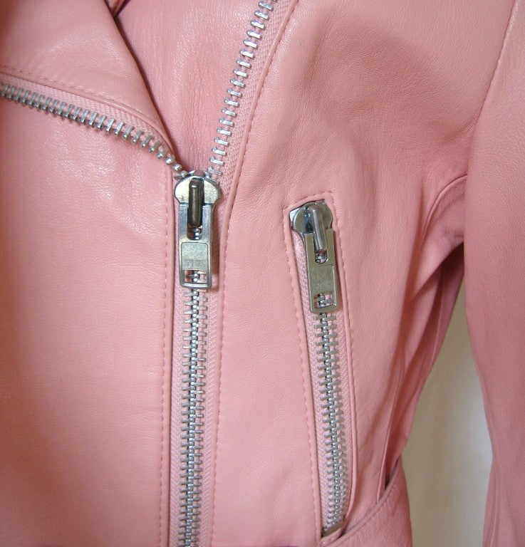 Michael Hoban for North Beach Leather pink leather motorcycle jacket with a detachable belt. It has bold silver zippers at front, pockets and wrists.  There are triangular stud detail at shoulder epaulettes, belt loops and back yoke. Fully lined,
