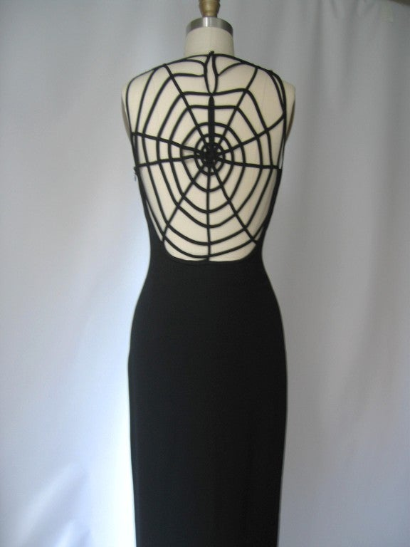 Simple long black fitted sheath with the wow factor being the back intricately detailed spider web design. Side zipper, fully lined, front shoulders slightly cut in and center back slit for walking ease. Fits 4-8