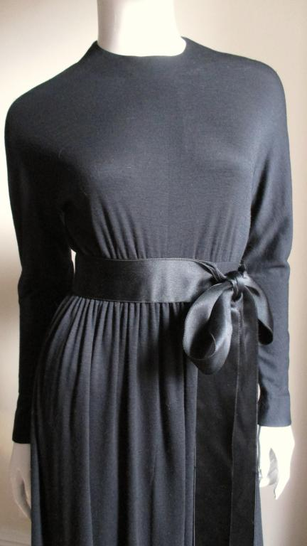 Attributed to Norman Norell with the model's name still in the neckline from a long ago fashion show.  A light weight black fine wool jersey dress with a silk satin ribbon adorned high waist.  Dolman sleeves to fitted, zippered wrists and a fuller