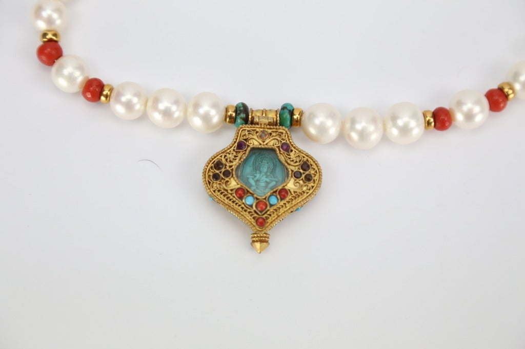 A Beautiful One-of-a-Kind large Pearl Necklace inter-space with Coral, Turquoise and Gold beads, suspending a Tibetan Prayer Box (Gau) Pendant, opens to reveal a seated Turquoise Buddha; handmade gilded sterling silver, inlaid with natural Turquoise