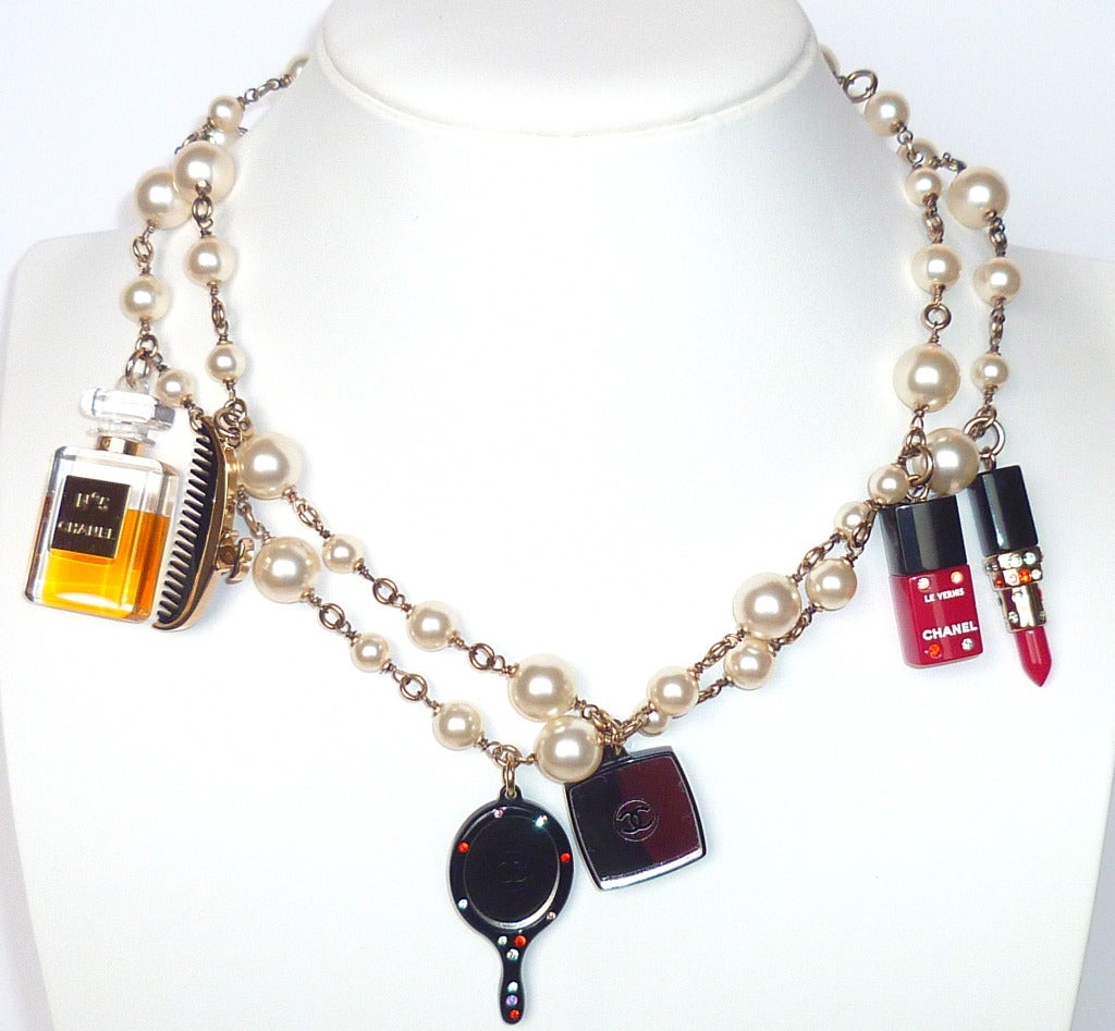 "A Fall 2004 Chanel pearls and multiple charm sautoir of cosmetics and perfume theme. Pearls and charms in perfect condition. Printed ""Chanel 94 A "" on bottom of the mini Chanel bottle. Length 38 inches. Bottle charm height 1 7/8 inches. Excellent"