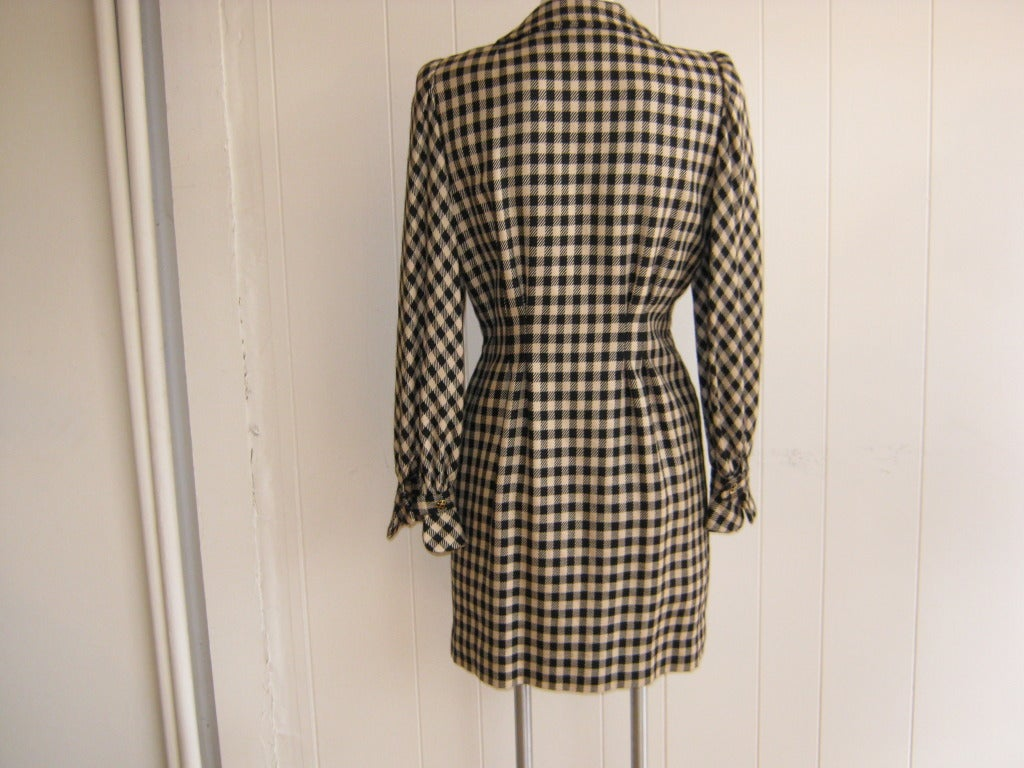 A French transplant to the US, Trigere spent seven decades designing small collections. This wool cream and black checked dress (a material Trigere favored), is repleat with details, from the front snap and hook and eye closure, to the fan shaped