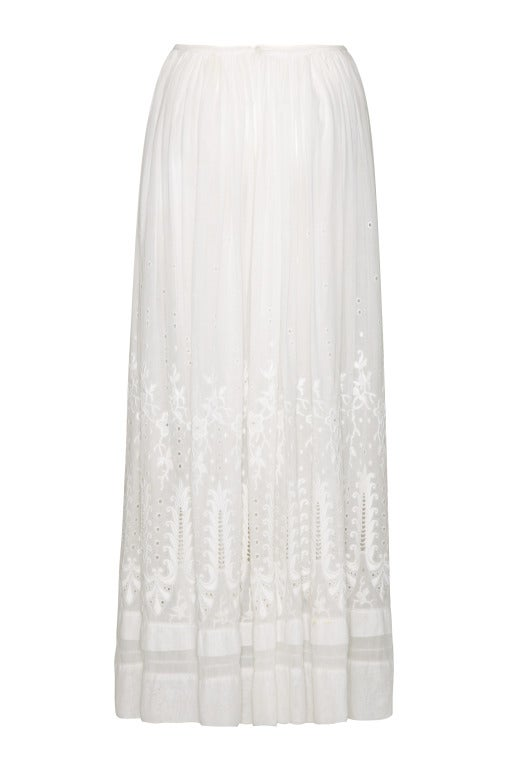 Beautiful sheer white cotton full - length Edwardian skirt circa 1910.  This piece is extremely decorative and features large satin stitch embroidery and eyelet work all over.  The skirt is gathered into a waist band, which fastens with a button,
