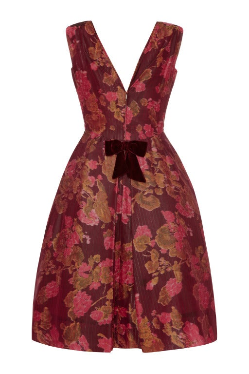 This fabulous dress by Elizabeth Arden was most probably designed by Oscar de la Renta whilst he was the Head Designer in 1961-63.  The dress is made from stunning plum coloured silk taffeta with a pink floral print and and fine green metallic