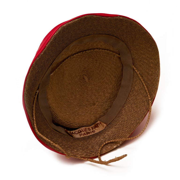 This finely woven straw hat is rimmed with a ruched cherry red made from 100% silk jersey. The interior has a straw covered wire frame to help keep the hat secure on the head. Jaque fath was a leading couturier from 1937-1952 and designed costumes