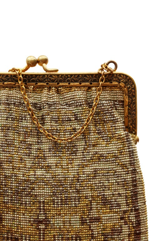 "This early 1920's kid leather lined flapper bag is comprised of extraordinary gold, silver and brown beadwork.  It has a gilt frame, chain handle and ball clasp.  In excellent antique condition It measures 14cm/5.25"" wide and 16.5cm/6.25"" long (not"