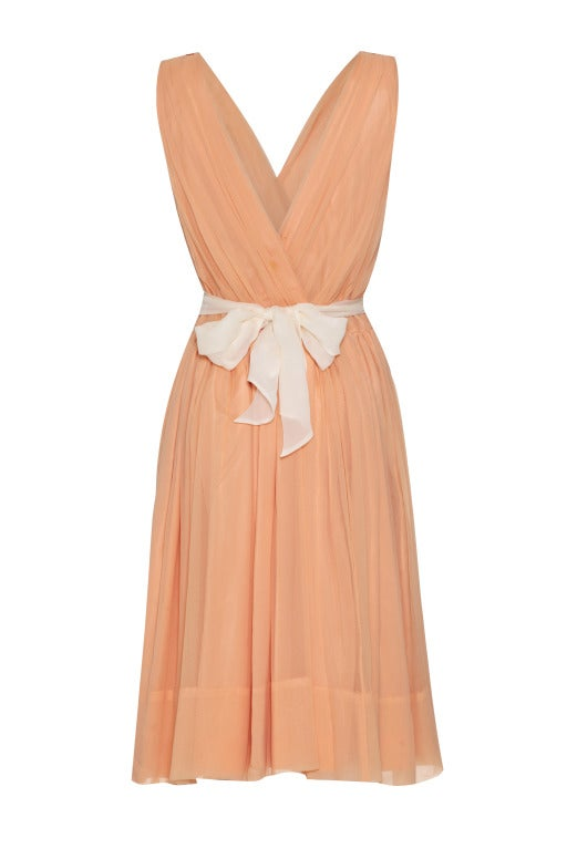 This gorgeous peach 1950's silk crepe dress by Minx Modes is taffeta lined with a deep 'v' crossover bodice and deep 'v' at the back.  It comes with its original cream fabric belt which is pictured tied at the back but looks equally beautiful at the