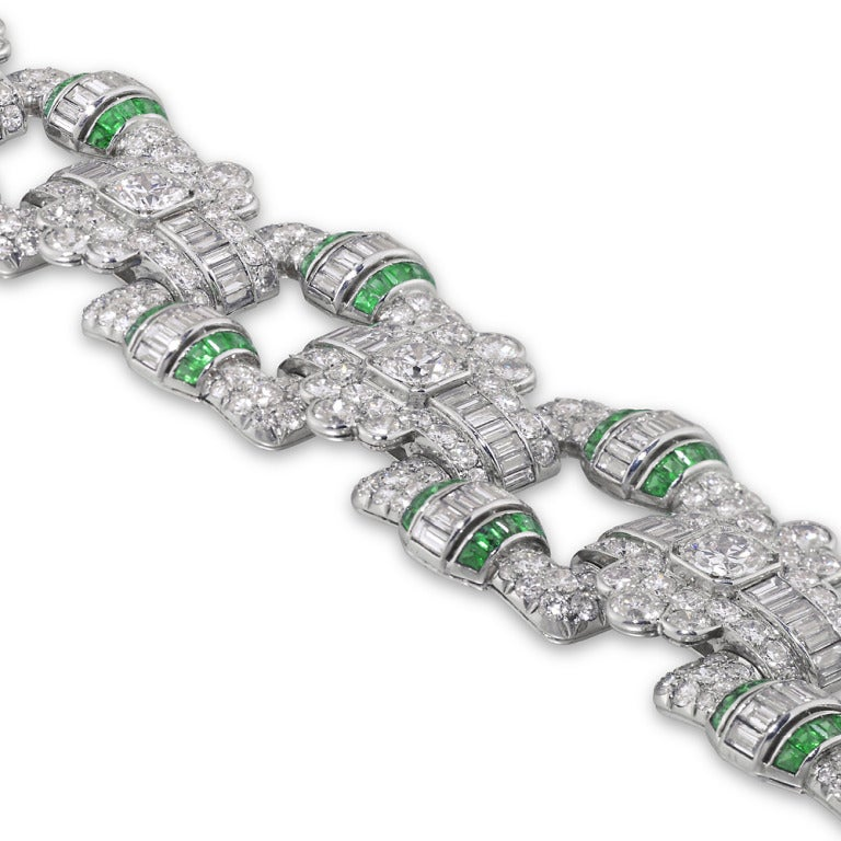 An important Art Deco emerald and diamond open panel bracelet, the bracelet comprised of six square open panels of a geometric design, with fancy lozenge-shaped links, encrusted throughout with brilliant- and baguette-cut diamonds, estimated to
