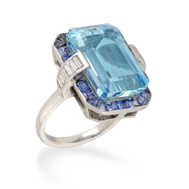 An aquamarine, sapphire and diamond cluster ring, the emerald-cut aquamarine weighing 13.05 carats, set to the centre of a sapphire cluster surround, eight graduated baguette-cut diamonds channel-set to each shoulder, weighing a total of 0.75