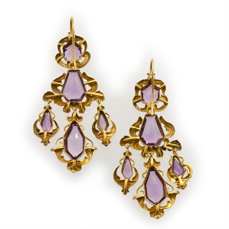 A pair of Victorian amethyst and repousse gold scroll motif earrings, each drop comprising a hexagonal-shaped faceted amethyst to the top, a kite shaped faceted amethyst to the centre with three graduated amethyst drops beneath weighing a total of