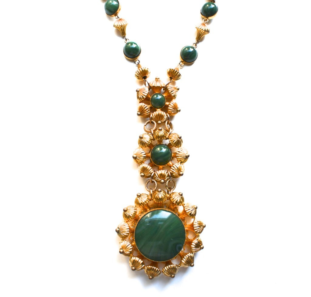 William De Lillo green glass Etruscan modern style bead necklace.  Signed on the back of the clasp. Features glass and lucite inserts. The main cabochon appears to be glass while the others are lucite. 18″ chain. Pendant is about 5 3/4″ Long. Width